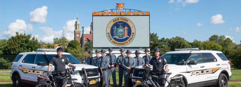 Officers in uniform lined up with UPD vehicles and bikes, in front of large digital scoreboard showing University Police emblem.